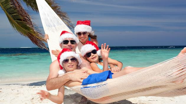 Family wearing Santa hats on a tropical beach