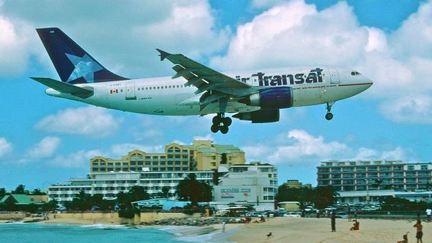A vintage photo, circa 2004, of an Air Transat A310 in the airlines old livery, flying over Maho Beach on arrival at Princess Juliana International Airport (SXM) in Sint Maarten.