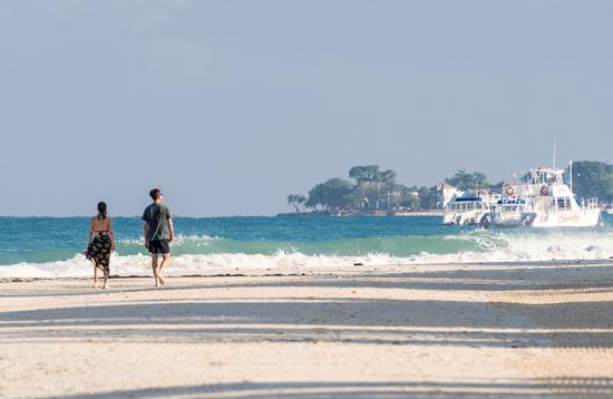 Couple walking Seven Mile Beach in Negril, Jamaica