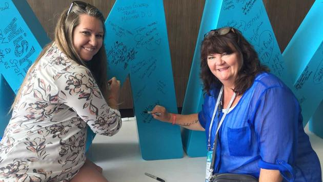 Heidi Henry, left, and Kelly Burnett of Travel by Kelly in Bristol, R.I., sign their names on the large SUMMIT letters as part of The Mark Travel Corp. Summit at the Grand Moon Palace Cancun. (Courtesy of Theresa Norton)