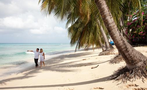 Couple walking on the beach in Barbados