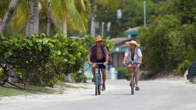 Two people riding bikes through Out Island, Bahamas