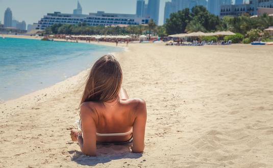 Woman relaxing on the beach in Dubai