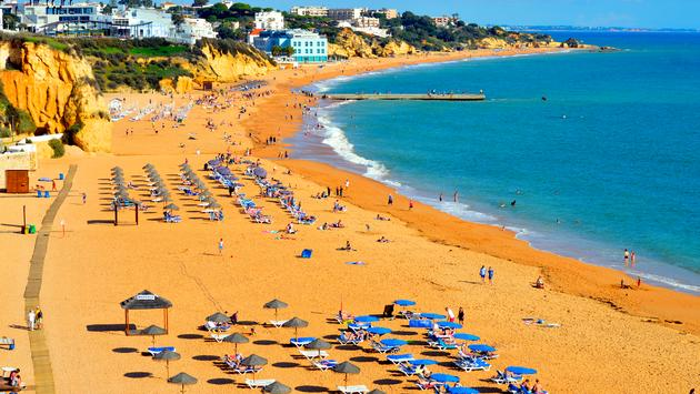 People enjoying the sun on the beach in Albufeira, Portugal