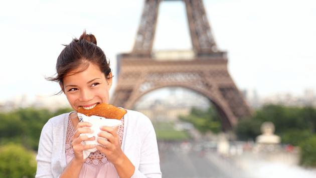 Woman enjoying street food in front of the Eiffel Tower in Paris, France