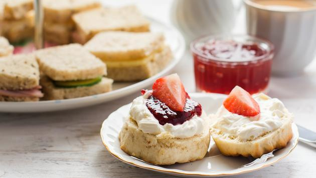 Traditional English afternoon tea: scones with clotted cream and jam, strawberries, with various sandwiches on the background, selective focus. (photo courtesy of Aiselin82 /iStock / Getty Images Plus)