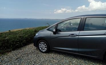 Rental car parked by the sea in Wales.
