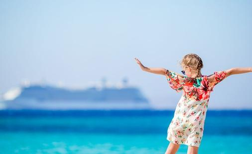 little girl at beach with cruise in background