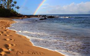 'Aloha' on Hawaiian beach beneath a rainbow.
