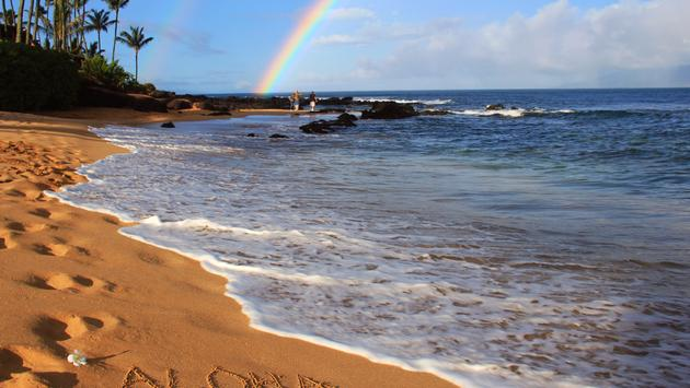 'Aloha' on Hawaiian beach beneath a rainbow.