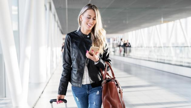 walking in airport and looking at mobile phone