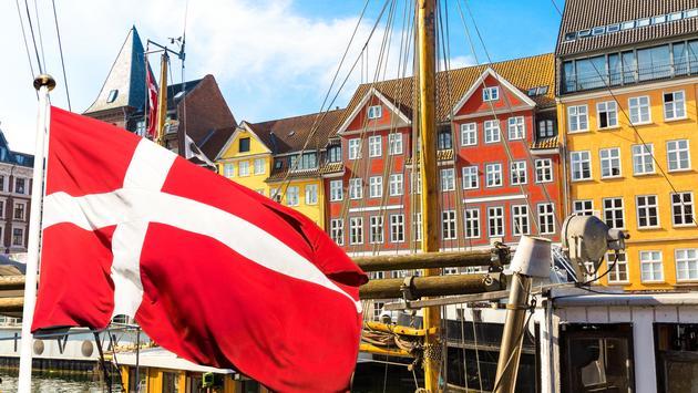 Denmark's national flag flying in the foreground of Copenhagen's famous old Nyhavn port.