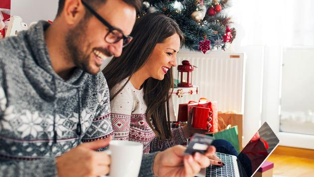 Buying Holiday gifts from home with credit card (Photo via Jelena Danilovic / iStock / Getty Images Plus)