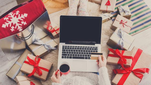 Woman makes christmas shopping online with laptop, above view (Photo via Milkos / iStock / Getty Images Plus)