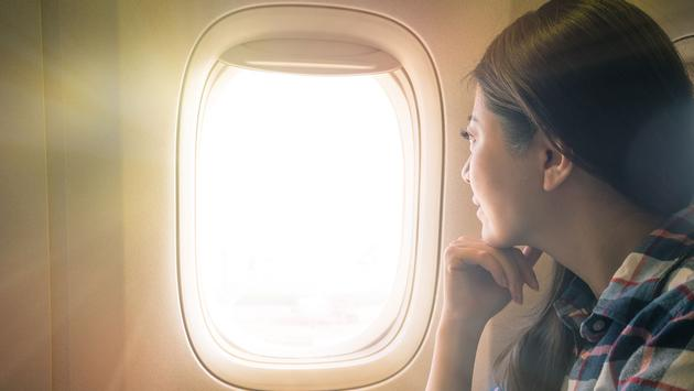 Woman looking out airplane window (Photo via PRImageFactory / iStock / Getty Images Plus)
