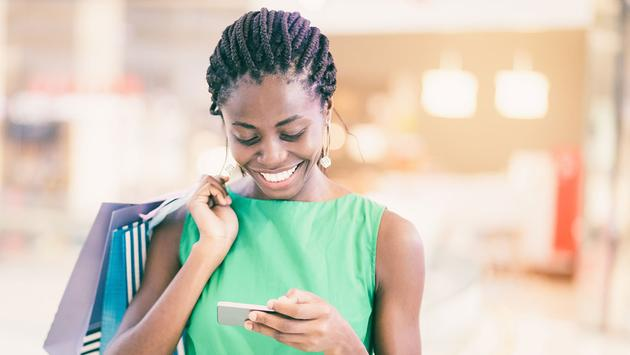 Smiling woman using phone in shopping mall (Photo via MangoStar_Studio / iStock / Getty Images Plus)