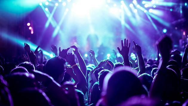 Crowd raising their hands at concert (Photo via bernardbodo / iStock / Getty Images Plus)