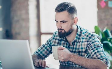 Man looking at his computer, holding mug (Photo via Deagreez / iStock / Getty Images Plus)