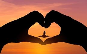 Silhouette of heart-shaped hands around an airplane at sunset