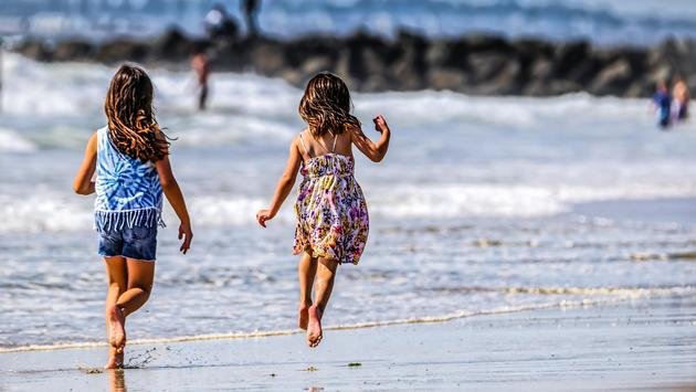 Young girls running down Imperial Beach near San Diego, California