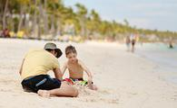 Father and son playing in the sand in Punta Cana, Dominican Republic