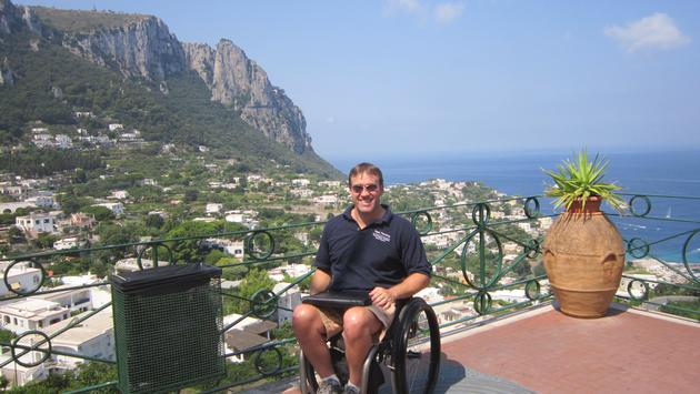 Traveler in a wheelchair posing in Capri