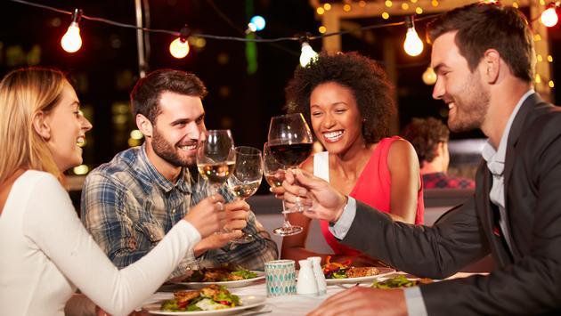 Friends enjoying dinner at an outdoor restaurant