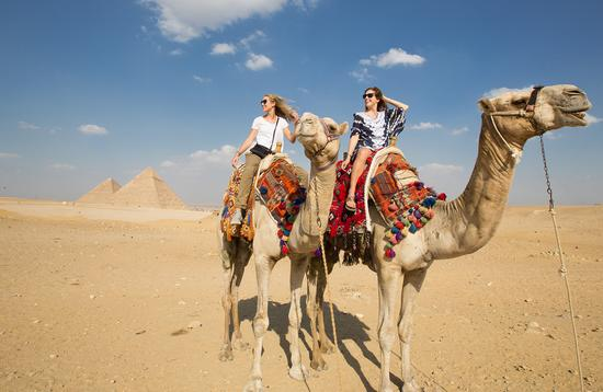 Egypt, Giza, Guests riding camels near the Great Pyramid of Giza