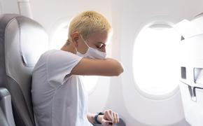 Woman covers a sneeze on an airplane