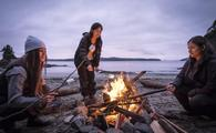 A family by the campfire in Bamfield, Vancouver Island, British Columbia, Canada