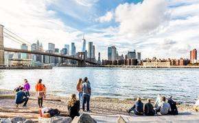 People enjoying the New York City skyline from the Pebble Beach shore