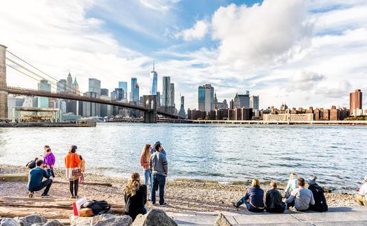 People enjoying the New York City skyline from the Pebble Beach shore