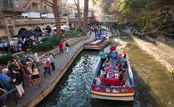 Tourist boats navigate the San Antonio River