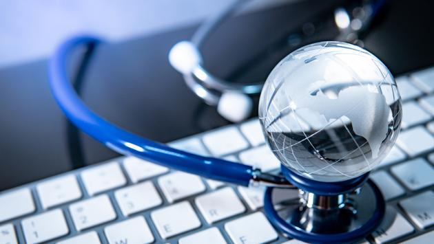 World globe crystal glass on blue stethoscope on white keyboard.