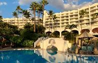 White resort hotel Fairmont Kea Lani during sunset with view of blue resort pool.