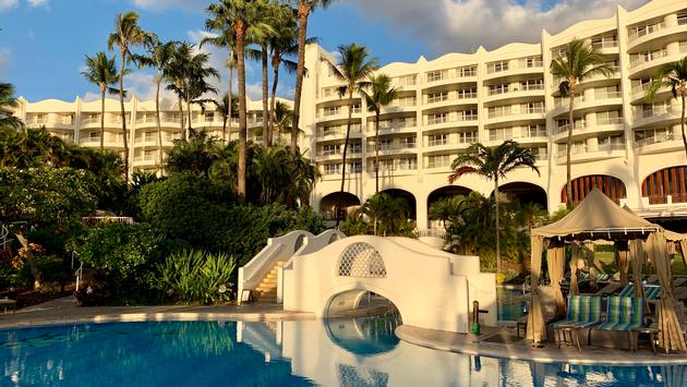 White resort hotel Fairmont Kea Lani during sunset with view of blue resort pool.