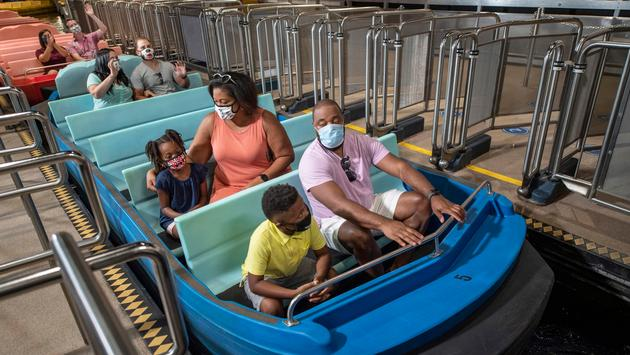 Disney guests on ride with masks.