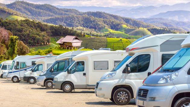RVs lined up in front of a green landscape.