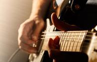 Close up of mans fingers playing electric guitar