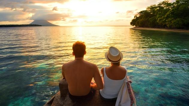 Happy couple relaxing at sunset