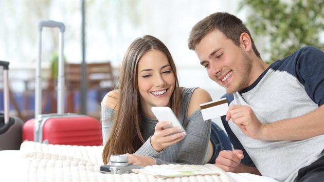 Tourists booking a hotel online with a credit card