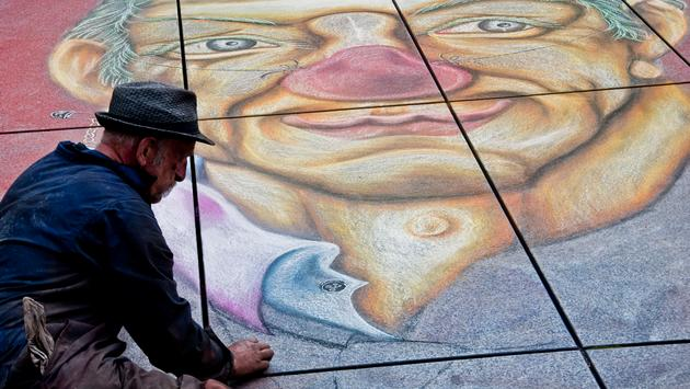 A homeless man painting a self-portrait in Paris, France