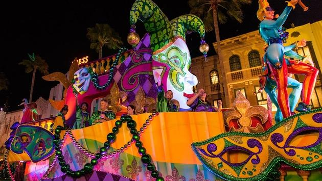 Guests catching beads from Mardi Gras parade float