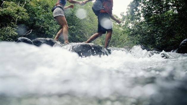 Man and woman hiking across a river in Maui, Hawaii