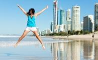 A woman jumps for joy on the beach in Gold Coast, Australia