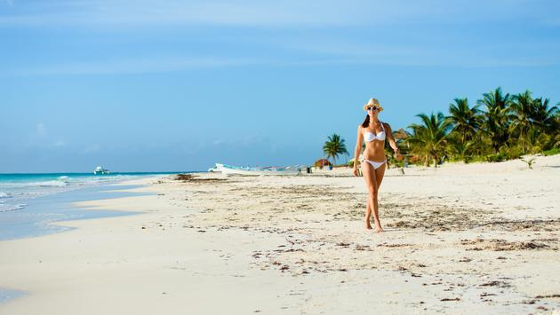 A woman walks on the beach in Riviera Maya, Mexico