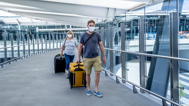 Travelers wearing masks at the airport