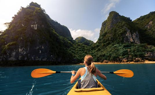 A woman exploring Vietnam's Ha Long Bay by kayak