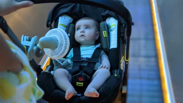 Battery-powered fan attached to a stroller walking through the airport