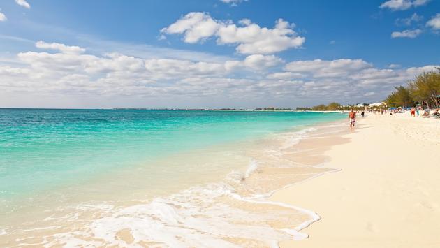 Tourists enjoying Seven Mile Beach in Grand Cayman